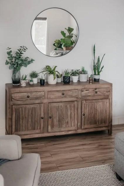 Eine-rustikale-Holz-Konsole-mit-vielen-Topfpflanzen-und-Grün-ist-eine-hübsche-Idee-um-Frühlings-Feeling-in-den-Raum-zu-holen