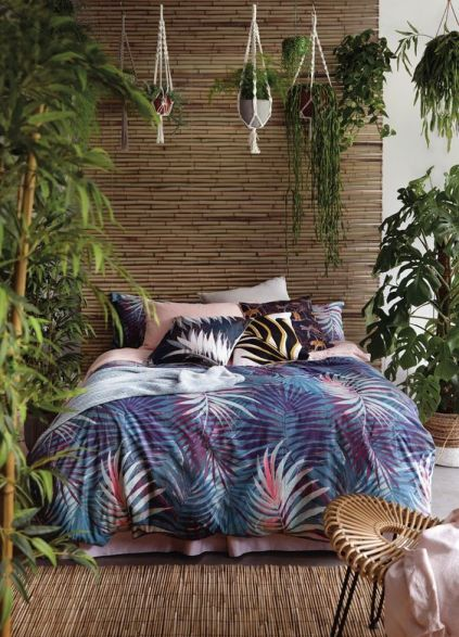 A-single-bamboo-wall-a-bamboo-rug-lots-of-potted-greenery-and-bright-tropical-bedding-create-an-ambience