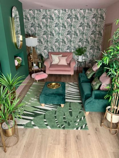 A-small-tropical-living-room-with-a-tropical-leaf-wall-a-green-sofa-and-ottoman-a-pink-chair-touches-of-gold