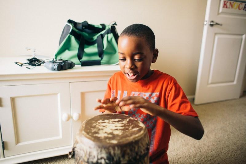 Black boy playing African drum black kids music article