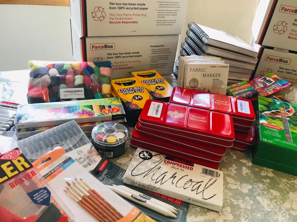 Collections of arts materials. Watercolour tin, paintbrushes, thread, felt, charcoal, sketchbooks, colouring pencils and acrylic paints