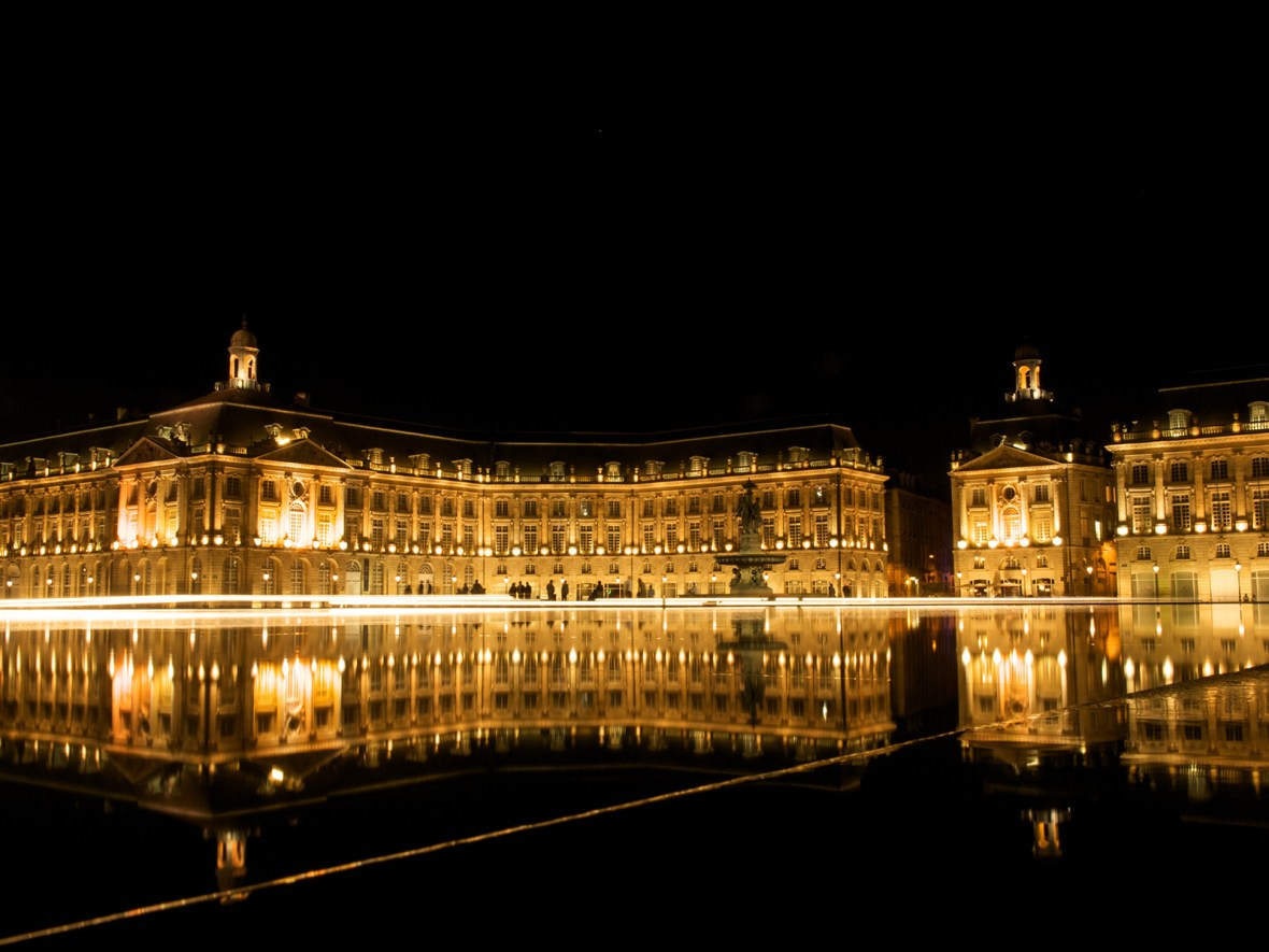 a night shot with water reflection of the buidlings around Place De La Bourse in Bordeaux, France
