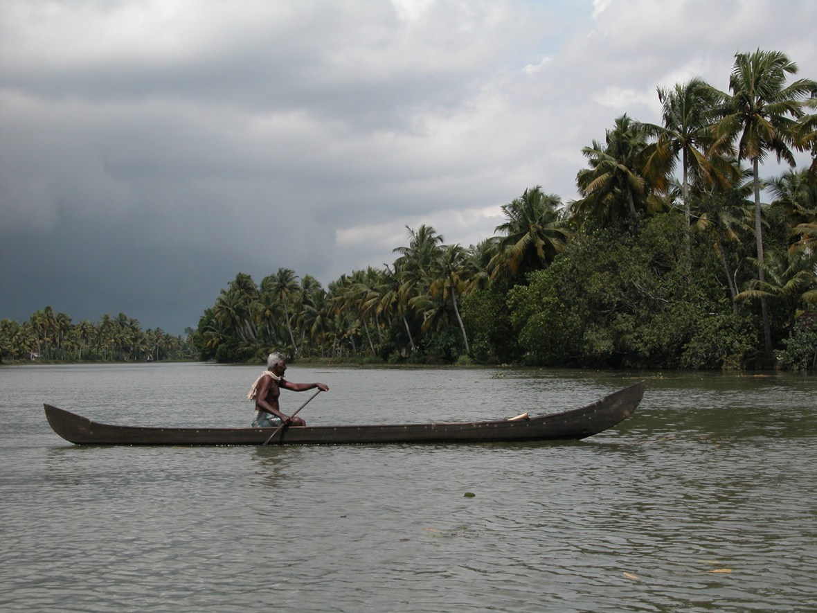 a man on a canoe trying to get home before the storm in Kerala's backwaters, in south India