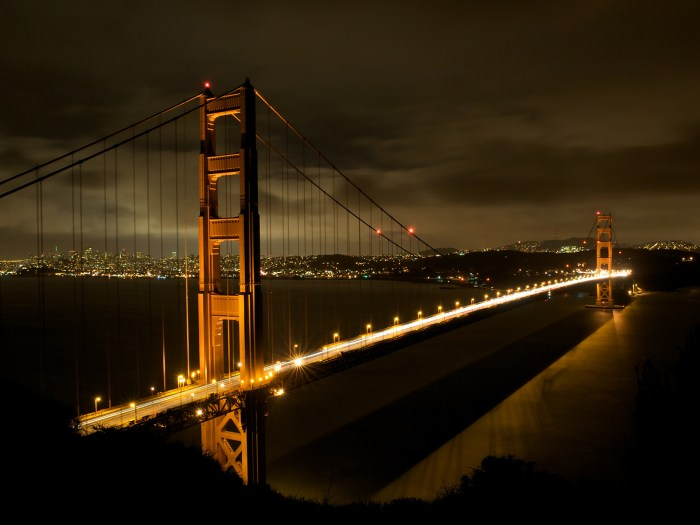 night shot of the Golden Gate Bridge with car lights streaking by in San Francisco, California, USA