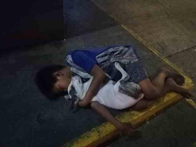 En las imágenes se pudo apreciar al niño, descalzo; vestido con un short y camisa de manga corta, abrazado a un perro, dormido entre sus brazos