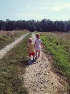 rodzeństwo na polnej drodze trzyma się za rączki