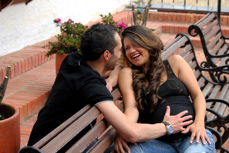 ciąży siedzi na ławce, śmieje się, mężczyzna trzyma rękę na brzuchu kobiety, śmieje się razem z nią