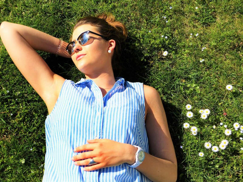 kobieta w okularach leży na trawie