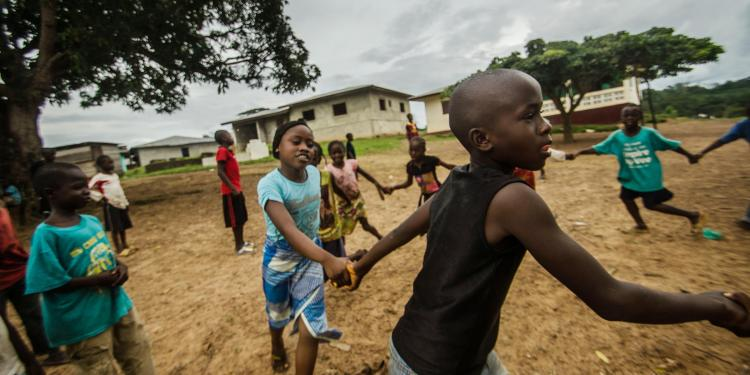 Mariama and Fomba Kanneh play in an open space in Barkedu, Liberia. With schools closed across the country,many kids spend their time playing outside every day