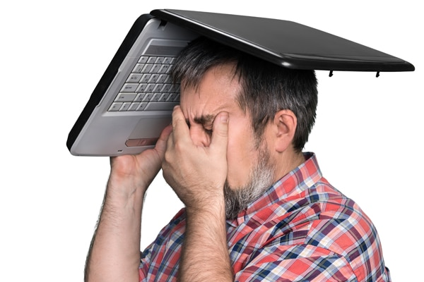 Man with his hand in his face and laptop open over his head