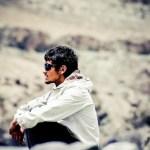 冬の野外で座り込むサングラスを掛けた男性