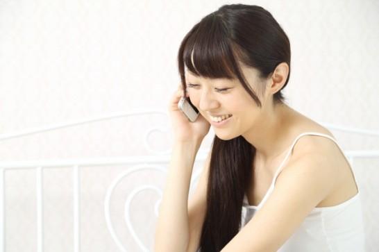 自宅で携帯電話で話す女性