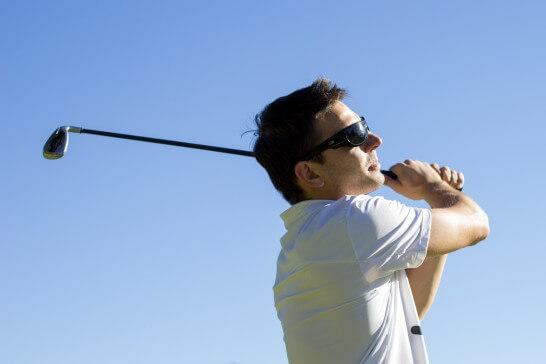 ゴルフのスイングをする男性