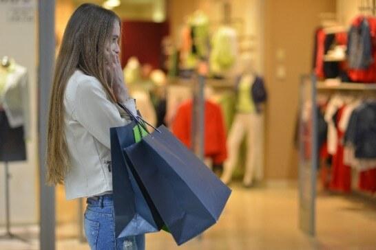携帯電話で電話するショッピング中の女性