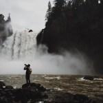 滝の前でカメラを構える男性