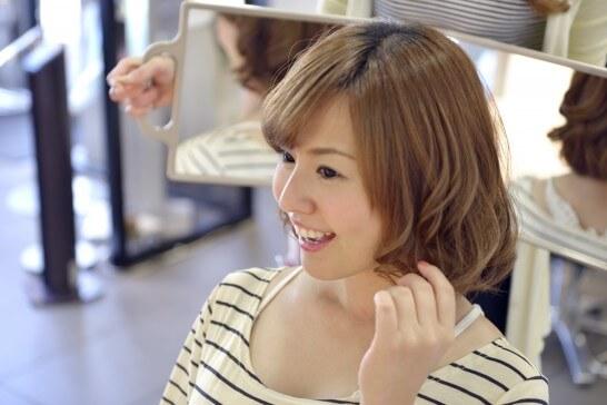 ヘアケア後の髪の仕上がりを確認する女性
