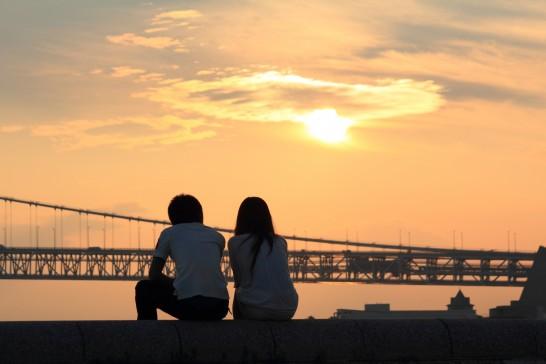 夕焼け時に橋の前で座る男女