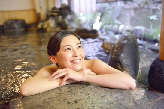 露天風呂に浸かる笑顔の女性
