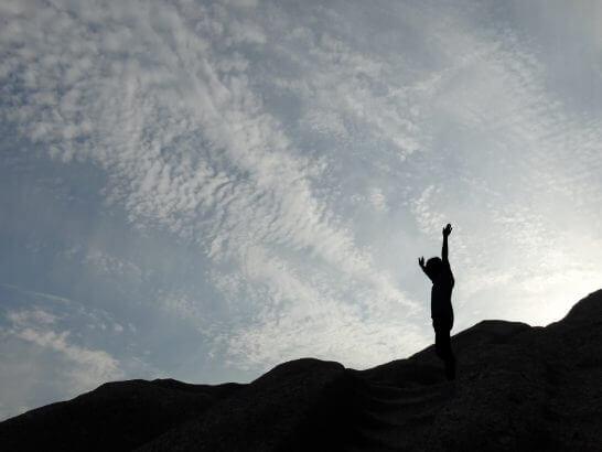 空に向かって手を広げる人