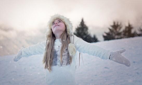 雪がちらつく中で手を広げる女子