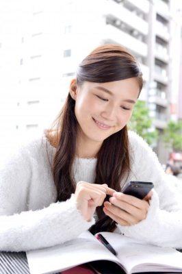 携帯電話をタッチする笑顔の女性