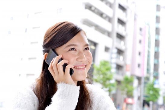 スマホで電話する笑顔の女性