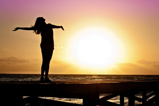 海岸で手を広げる女性