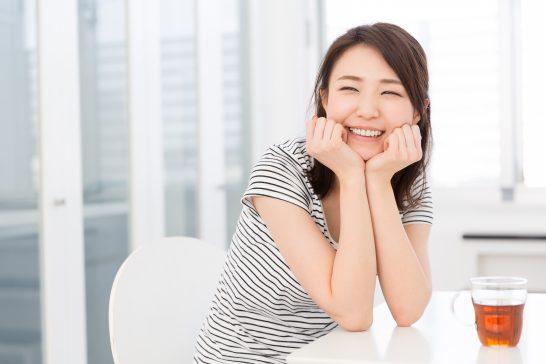ほおづえをつく笑顔の女性