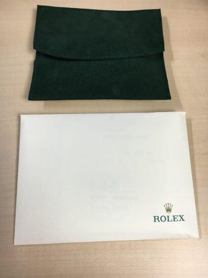 修理したロレックスが入っている袋と書類入れ
