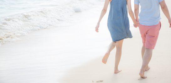 海辺で手をつないで歩く男女