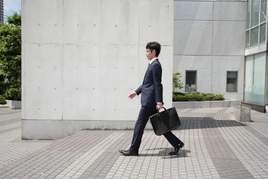 カバンを持って歩くビジネスマン