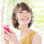 スマートフォン(スマホ)を持つ笑顔の女性