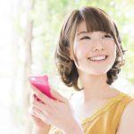 スマートフォンを持つ笑顔の女性