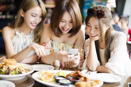 レストランで食事をしながらスマホを見る女性