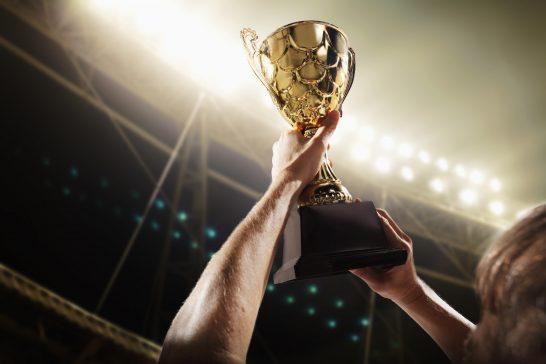 チャンピオンのトロフィーを掲げるアスリート
