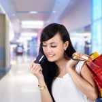 クレジットカードを見せるショッピング中の女性