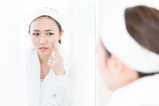 肌を気にして考える女性