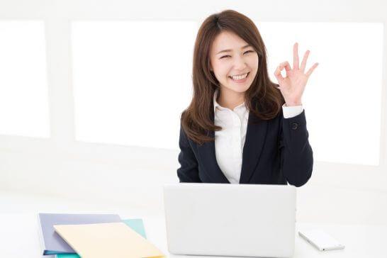 OKポーズを取るOLの女性 (パソコンの前)