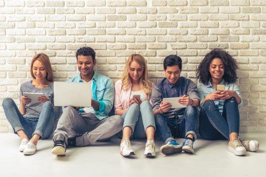 座ってスマホ・タブレット・パソコンを見る人々