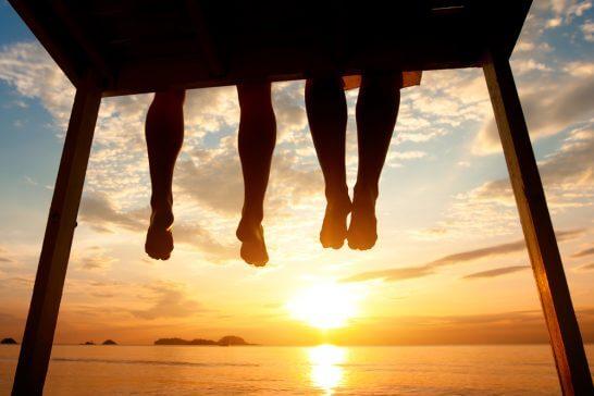 日差しの中、海岸で座る男女