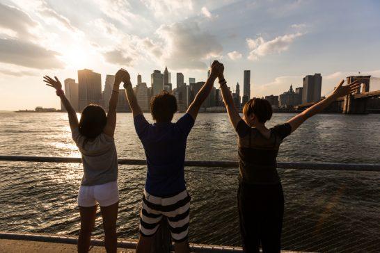 海外のニューヨークで手を合わせて広げる仲間