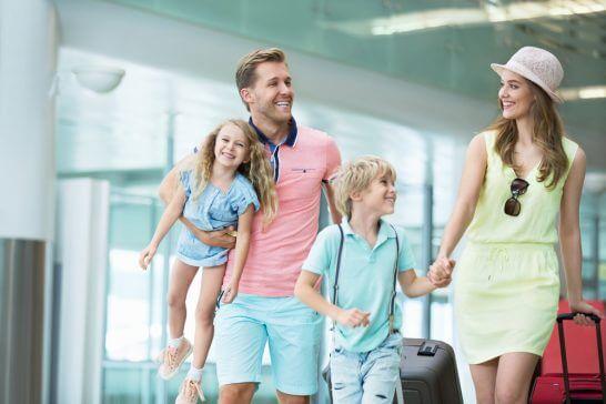 空港でスーツケース・手荷物を運ぶ家族