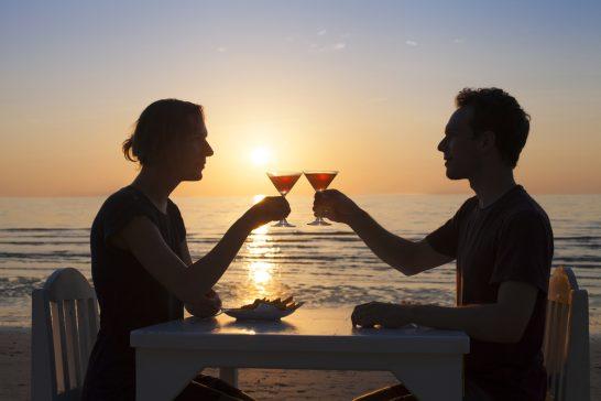 海辺で乾杯する男女