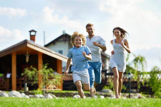 住宅をバックに走る家族