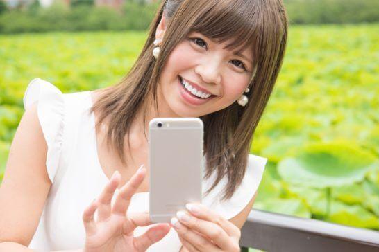 スマートフォンを操作する笑顔の女性