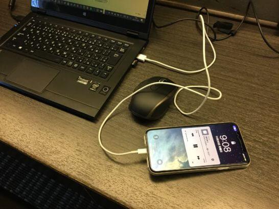 ホテルのテーブルの上にあるノートPCとiPhone X