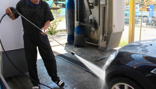 高圧洗浄機で車を清掃する男性
