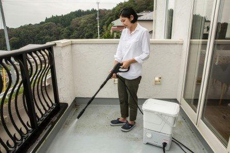 タンク式高圧洗浄機でベランダを掃除するシーン