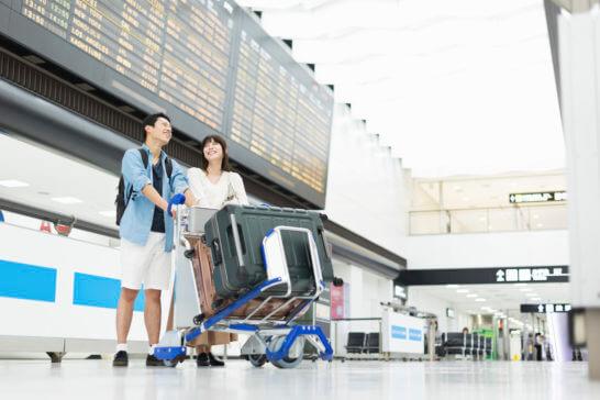 手荷物(スーツケース)のカートを押して空港を移動する家族