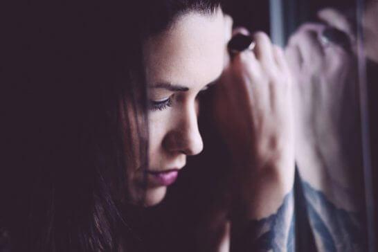 暗闇の中うつむいて考える女性